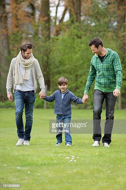 boy walking with two men in a park - familie mit einem kind stock-fotos und bilder