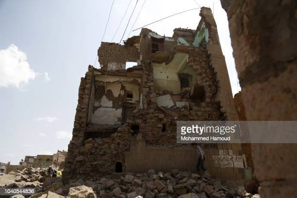 A boy walks by a house destroyed in an airstrike carried out by a Saudiled coalition warplane in the Old City of Sana'a on 2018 in Sana'a Yemen