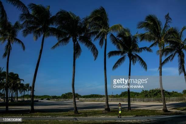 Boy walks by palm trees on the beach in Miami Beach, Florida on August 27 amid the coronavirus pandemic.