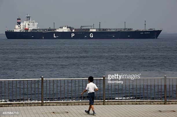 A boy walks by the waterfront in front of a liquefied petroleum gas tanker sailing to Tokyo Bay in Kisarazu Chiba Prefecture Japan on Tuesday July 22...