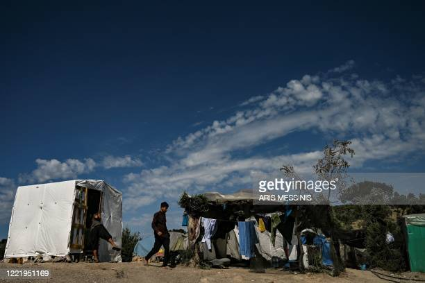 Boy walks in a improvised tents camp near the refugee camp of Moria in the island of Lesbos on June 21, 2020. - Greece's announcement that it was...