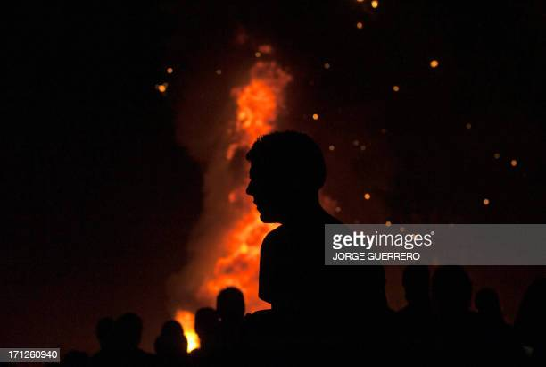 A boy walks in fron of a bonfire early on June 24 during the traditional San Juan's night in a beach of Malaga southern Spain Fires are lit...