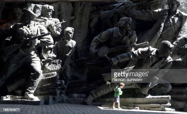 Boy walks in front of a monument of the WWII open-air museum in the Ukrainian capital Kiev on May 8 prior to the Victory Day celebration. AFP PHOTO/...