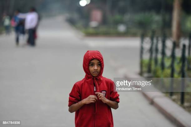 A boy walks in the premises of Raj Ghat on a cold and smoggy day on December 3 2017 in New Delhi India Delhi witnessed a sharp drop in temperature in...