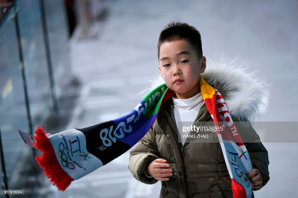 A boy walks in the stands during the curling mixed doubles semi-final during the Pyeongchang 2018 Winter Olympic Games at the Gangneung Curling Centre in Gangneung on February 12, 2018. / AFP PHOTO / WANG Zhao
