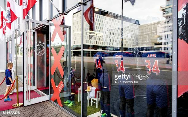 A boy walks into a store next to football jerseys bearing the words 'Stay Strong Appie' and the number 34 to show support to Ajax midfielder Abdelhak...