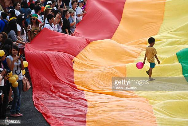 A boy walks on a rainbow flag during the Manila Gay Pride March on December 8 2012 in Makati Philippines Although frowned upon by the mainstream...