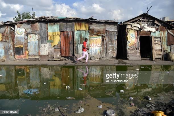 Boy walks on a street in the La Saline neighborhood of Port-au-Prince on October 26 close to the Market of La Saline. / AFP PHOTO / HECTOR RETAMAL