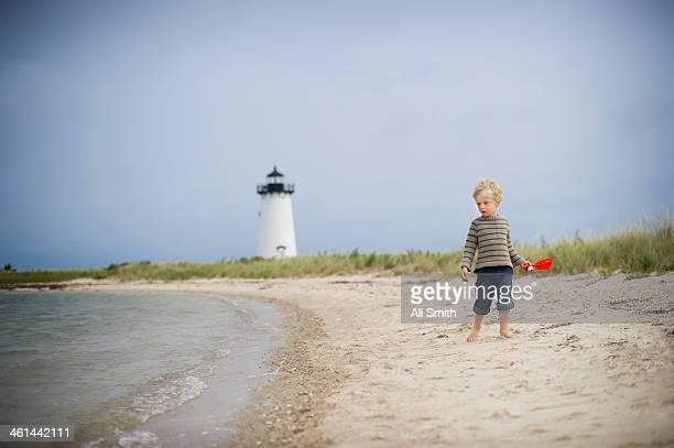 Boy walks on beach by lighthouse