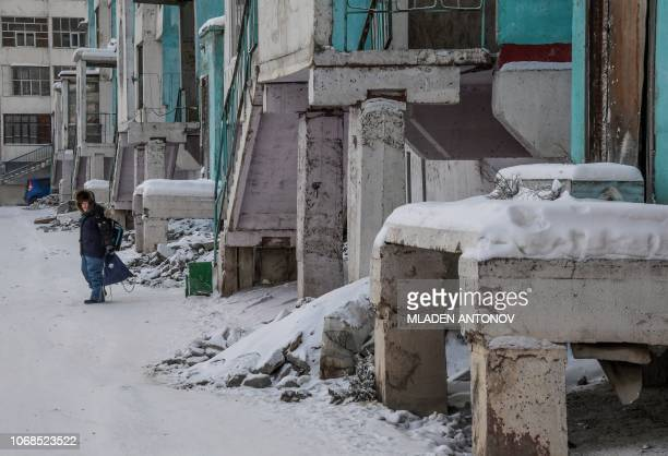 A boy walks out of a cracked panel apartment building in the eastern Siberian city of Yakutsk on November 26 2018 Many houses in Yakutsk are made up...