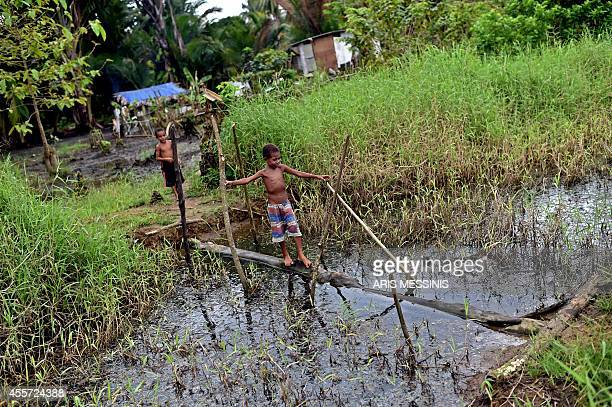 A boy walks outside his house in the town of Kerema Papua New Guinea on September 6 2014 AFP PHOTO / ARIS MESSINIS