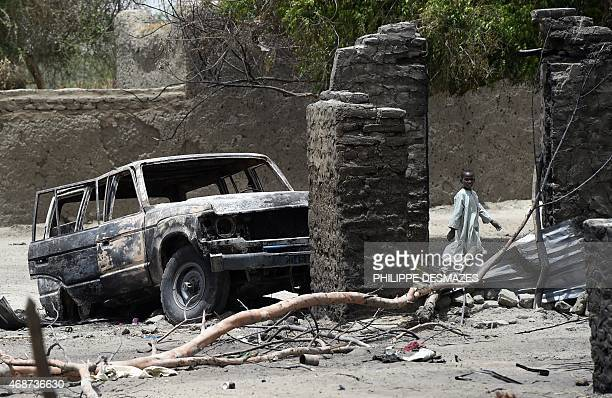 A boy walks past a burnt house and car on April 6 2015 in N'Gouboua near Lake Chad in Chad which was attacked by Islamist group Boko Haram on...