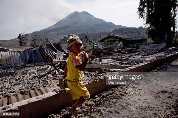 A boy walks past a damaged house caused by the eruptions of Mount Sinabung as Mount Sinabung spews ash at Kuta Gugung village on February 11 2014 in...