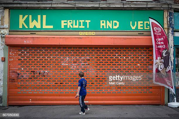 A boy walks past a shop that is closed on a housing estate in Bristol on August 3 2015 in Bristol England