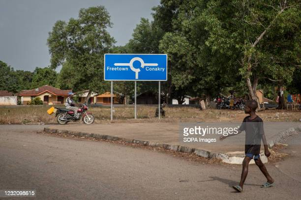 Boy walks past a signpost that points to both Sierra Leone capital Freetown and Guinea's capital Conakry. The latest Ebola outbreak in Guinea was...