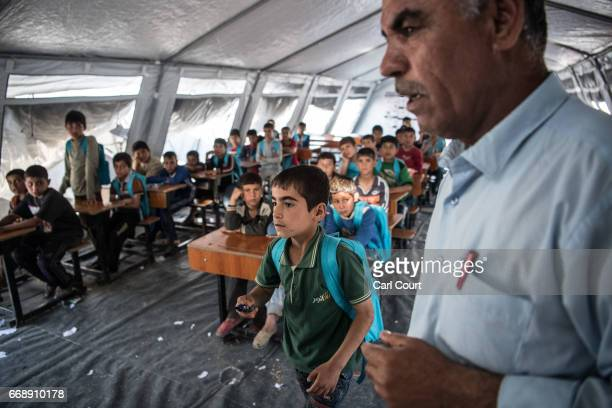 A boy walks past a teacher to write on a whiteboard in class at a school in Khazir refugee camp on April 15 2017 near Mosul Iraq Khazir camp with a...