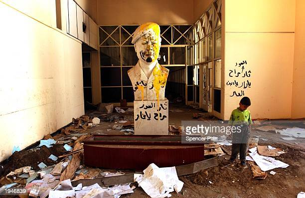 A boy walks past a vandalized Saddam Hussein statue in the looted Ministry of Culture April 23 2003 in Baghdad Iraq US troops arrested fighters of...