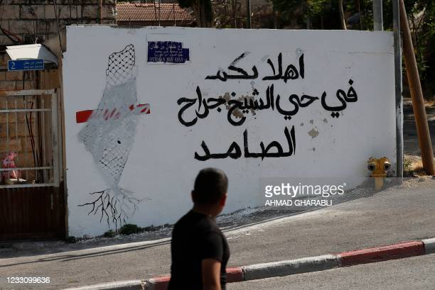 "Boy walks past Arabic slogan reading: ""Welcome in the intransigent Sheikh Jarrah neighbourhood"", on May 25 in the Israeli-annexed east Jerusalem..."