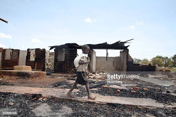 A boy walks past destroyed homes torched during clashes following the Kenyan elections in Eldoret Kenya on Saturday Feb 16 2008 As many as 400 people...