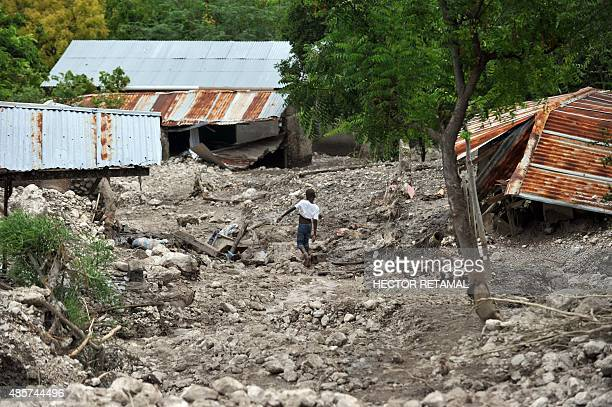 A boy walks past destroyed houses after a mudslide caused by the rains from Tropical Storm Erika in Montrouis Haiti on August 29 2015 Erika left at...