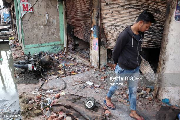 A boy walks past next to charred shops after it was set on fire by a mob during riots in Chandbagh area of New Delhi India on 29 February 2020 More...