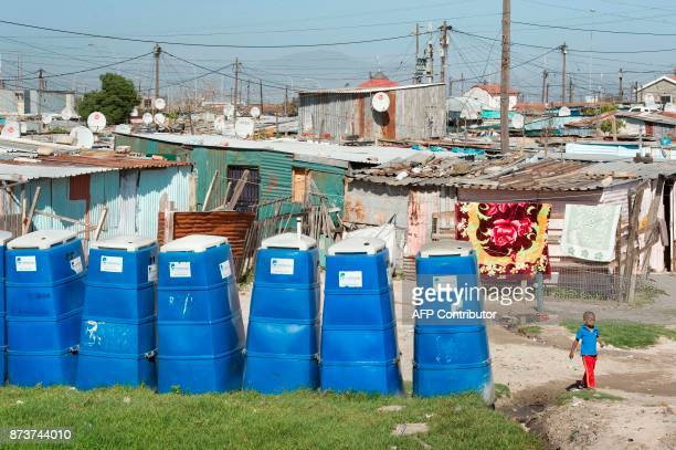 A boy walks past portable toilets at an informal settlement in Khayelitsha a mostly impoverished township about 35km from the centre of Cape Town on...
