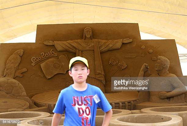 A boy walks past Sand sculpture of the famous Christ the Redeemer statue of Jesus Christ titled Rio 2016 Olympic at the site of Sand Museum in the...