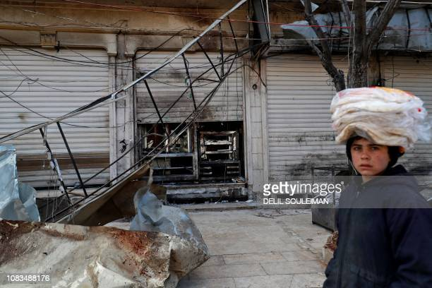 TOPSHOT A boy walks past the shuttered doors of a restaurant which was the site of a suicide attack targeting USled coalition forces in the...