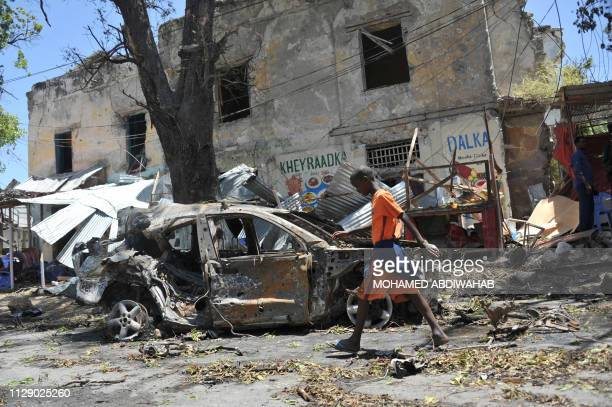 Boy walks past the site of a car bomb attack near a security checkpoint in the Somali capital, not far from the presidential palace in Mogadishu on...