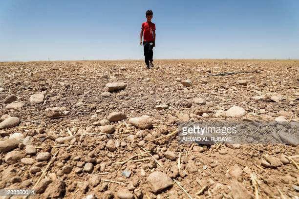 Boy walks through a dried up agricultural field in the Saadiya area, north of Diyala in eastern Iraq on June 24, 2021. - As Iraq bakes under a...