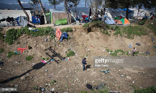 A boy walks through a gully at the Idomeni refugee camp on the Greek Macedonia border on March 20 2016 in Idomeni Greece Thousands of migrants remain...