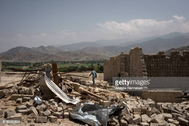 A boy walks through buildings damaged from fighting on July 15 2017 in Shadal Bazaar Afghanistan People are slowly returning to the recently...