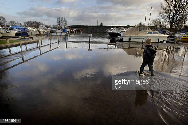 A boy walks through the water at a flooded parking lot near the marina along the Prinses Margriet Kanaal in Bergum on January 4 2012 The northern...