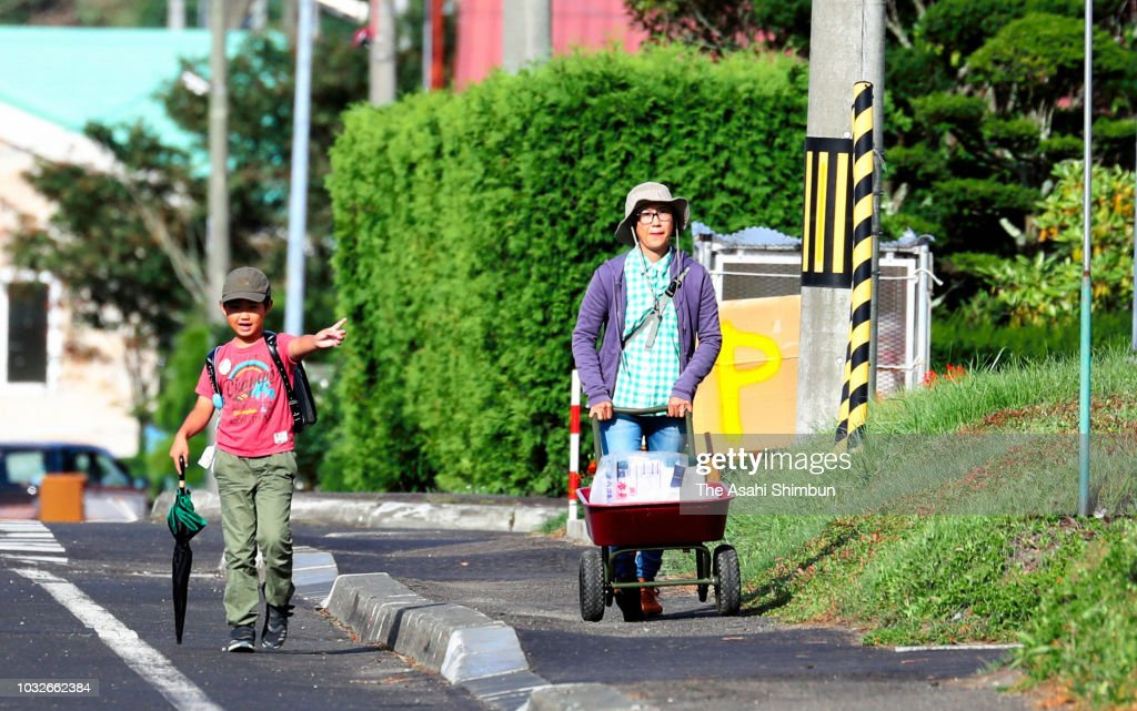 A boy walks to school with his mother, who is on the way to water distribution a week after the magnitude 6.7 earthquake on September 13, 2018 in Abira, Hokkaido, Japan. Concerns are rising about the health of the evacuees because prolonged life in shelters can pose serious risks. Living away from home and together with strangers puts enormous mental and physical strains on evacuees.