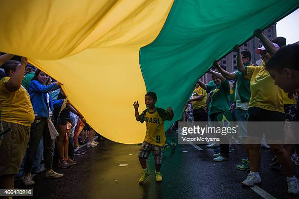 A boy walks under a flag as antigovernment protesters march along Avenida Paulista on March 15 2015 in Sao Paulo Brazil Protests across the country...