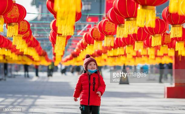 Boy walks under red lanterns set up at a pedestrian street to mark the upcoming Chinese New Year, the Year of the Ox, on February 6, 2021 in Hohhot,...