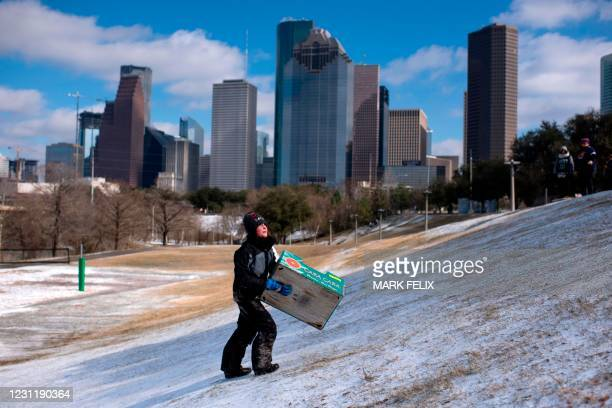 Boy walks up a snow covered hill after sledding down it in a box in Houston, Texas on February 15, 2021. - Much of the United States was in the icy...