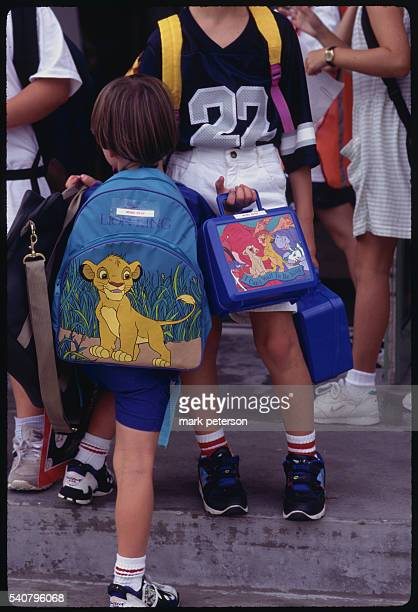 A boy walks with his backpack and lunchbox which contain cartoon characters from the Disney animation film The Lion King These children are residents...