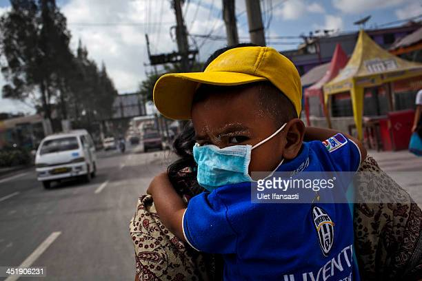 A boy waring a mask is carried through through an area covered by ash after Mount Sinabung erupted spewing volcanic materials at Berastagi village on...