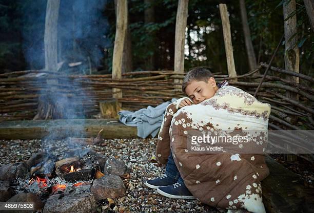 Boy warming himself with blanket