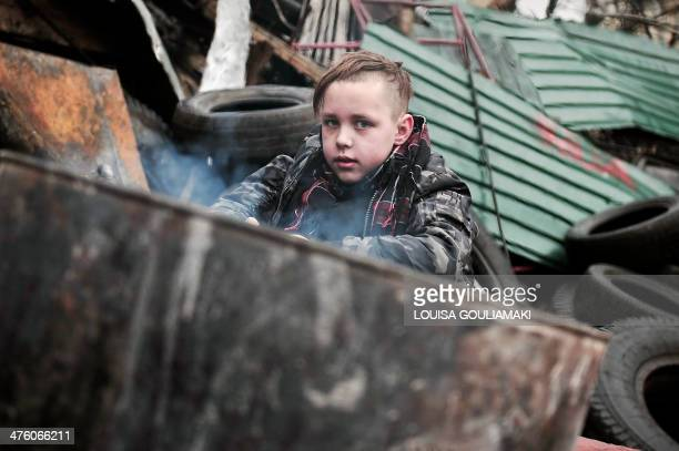A boy warms near a fire at a barricade in central Kiev on March 2 2014 Ukraine said Sunday it would call up all military reservists after President...