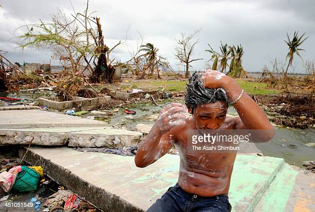 A boy washes his body on November 20 2013 in Tacloban Leyte Philippines Typhoon Haiyan which ripped through Philippines over the weekend has been...