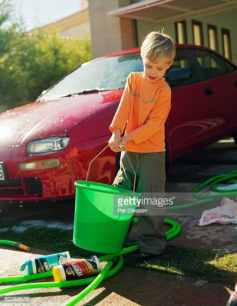A boy washing a red car.