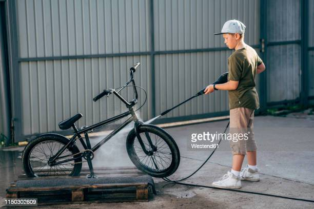 boy washing bmx bike with pressure washer on yard - high pressure cleaning stock pictures, royalty-free photos & images