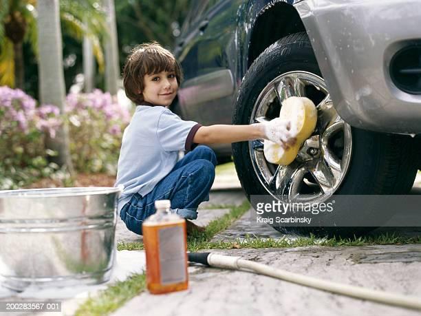 Boy (5-7) washing car on driveway, smiling, portrait