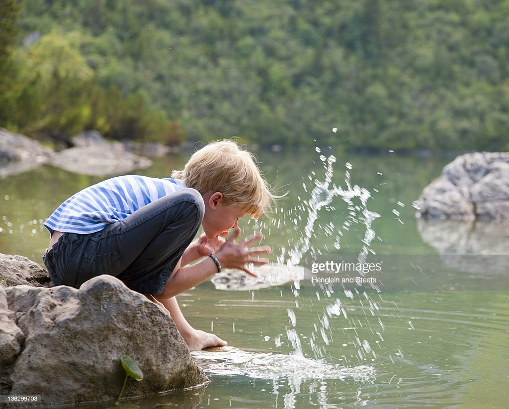 Boy washing his face in still lake : Stock Photo