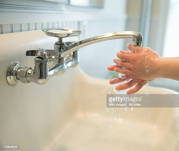 A boy washing his hands under the bathroom tap.