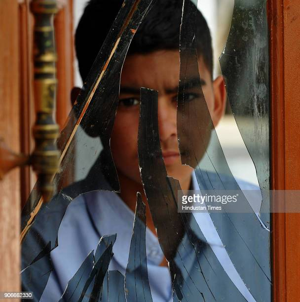A boy watches a broken glass of a window damaged in shelling from the Pakistan side on January 18 2018 in Arnia district of Jammu India Indian...