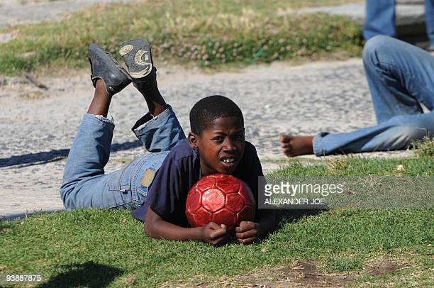 A boy watches a football match in the Gugulethu township outside of Cape Town on December 2 2009 With the draw for the World Cup 2010 turning Cape...