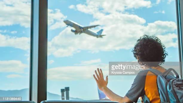 boy watches a plane take off by the airport window - nur jungen stock-fotos und bilder